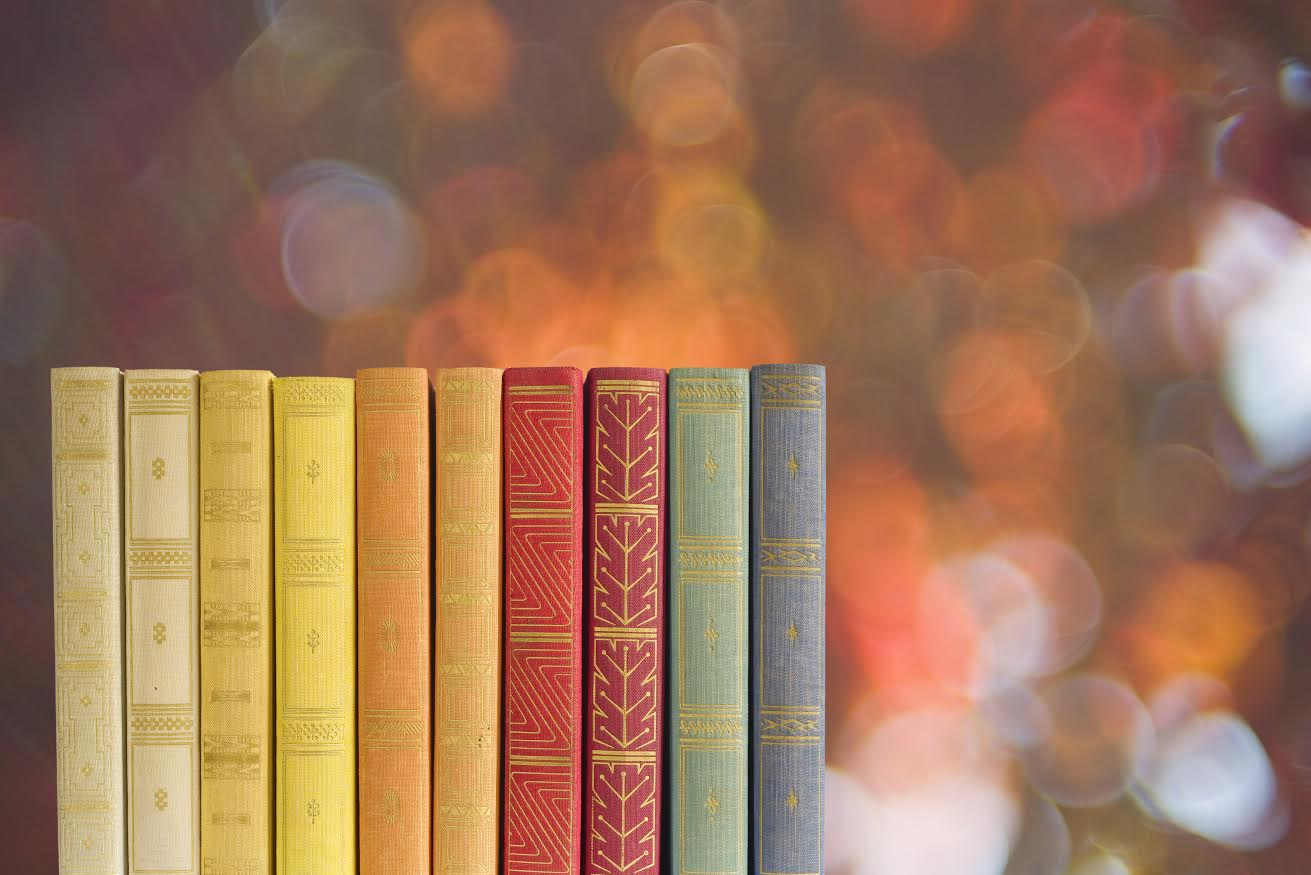 row of books on blurred nature background, free copy space